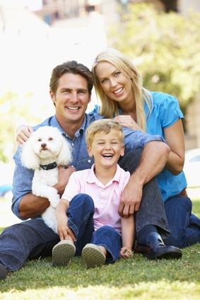 man, woman and son in the park with their white toy poodle